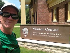 Rich Houston, history teacher in front of National Park Visitor Center sign